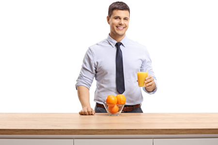 Young man wearing shirt and tie drinking orange and holding a glass of orange juice isolated on white background