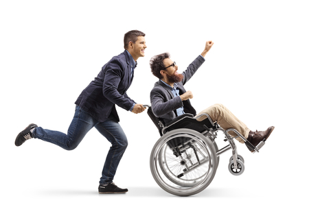 Full length shot of a young man running and pushing an excited man in a wheelchair gesturing with hand isolated on white background