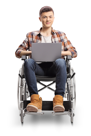 Smiling young guy in a wheelchair with a laptop isolated on white background Imagens
