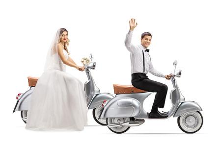 Colpo integrale di una sposa e dello sposo che guidano scooter vintage e che salutano isolati su sfondo bianco