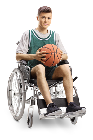 Full length portrait of a young man in a wheelchair holding a basketball and smiling at the camera isolated on white background
