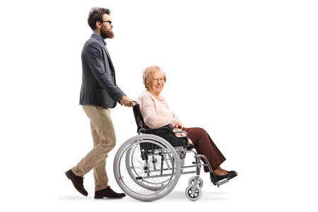 Full length profile shot of a bearded man pushing a senior woman in a wheelchair isolated on white background Banco de Imagens