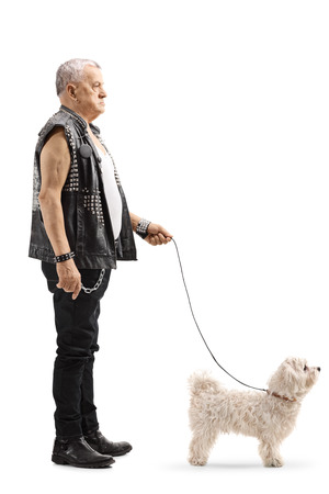 Full length profile shot of a mature punker standing with a little white dog isolated on white background 写真素材