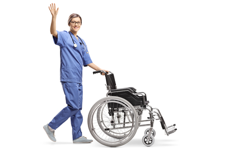 Full length shot of a young female nurse pushing an empty wheelchair and waving isolated on white background Imagens - 120156116