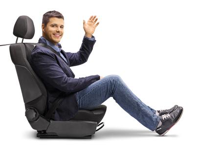 Volledige lengte shot van een jonge man in een autostoeltje met een vastgemaakte veiligheidsgordel met een stuur geïsoleerd op een witte achtergrond