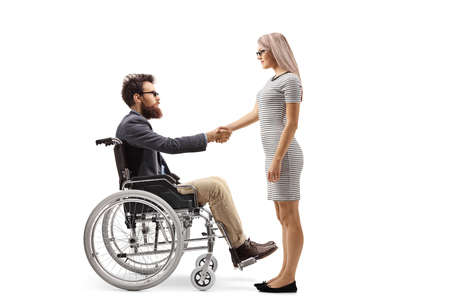 Full length shot of a bearded man in a wheelchair shaking hands with a young woman isolated on white background