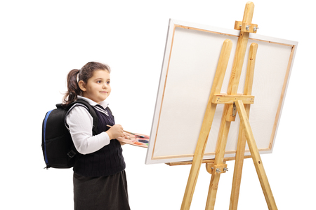 Little schoolgirl holding a color palette and a brush and standing in front of a canvas isolated on white background