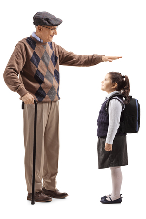Full length shot of a grandfather gesturing with hand and showing the height of his granddaughter isolated on white background 写真素材