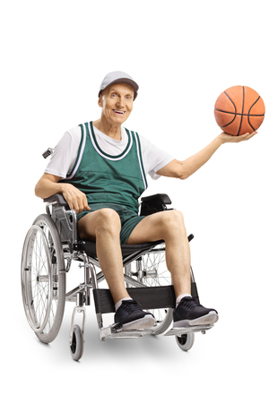 Senior disabled man in a wheelchair holding a basketball and smiling at the camera isolated on white background