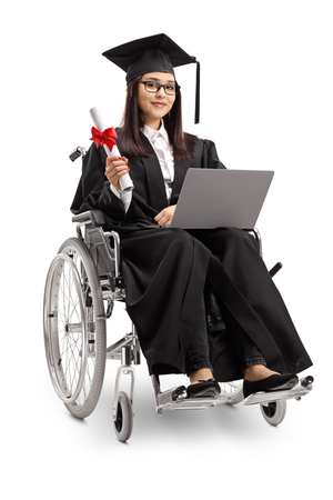 Full length shot of a young woman in a wheelchair wearing a graduation gown and holding a diploma and laptop isolated on white background Imagens