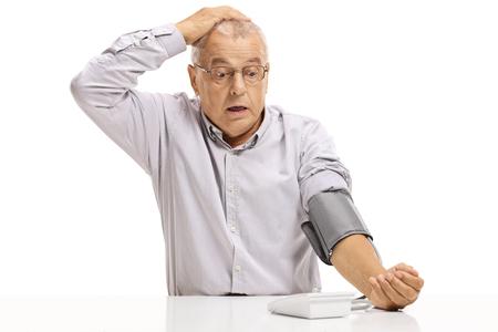 Schockierter reifer Mann, der isoliert auf weißem Hintergrund Blutdruckmessung durchführt