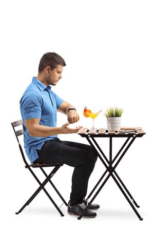 In voller Länge Profilaufnahme eines irritierten jungen Mannes, der in einem Café sitzt und seine Uhr einzeln auf weißem Hintergrund betrachtet