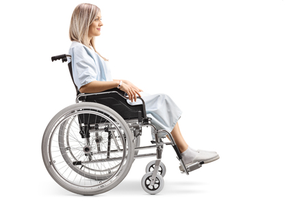 Full length profile shot of a young female patient in a wheelchair isolated on white backgraund