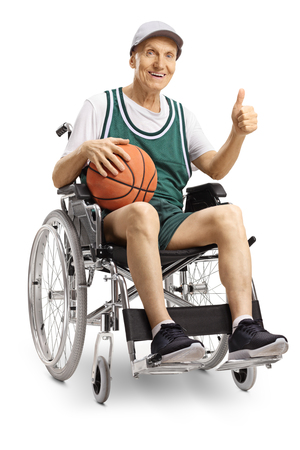Disabled elderly man in a wheelchair holding a basketball and showing thumbs up isolated on white background
