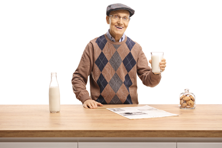 Elderly man holding a glass of milk and standing behind a wooden counter isolated on white background