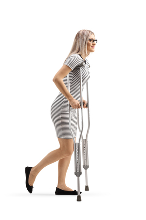 Full length shot of a young woman walking with crutches isolated on white background