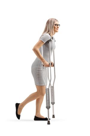Tourné sur toute la longueur d'une jeune femme marchant avec des béquilles isolé sur fond blanc