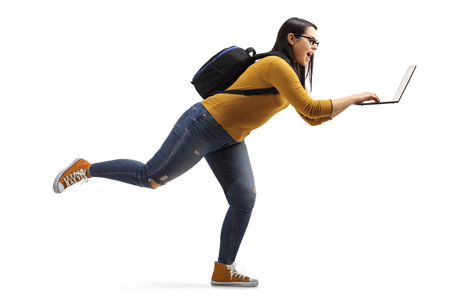 Full length profile shot of a female student running with a laptop isolated on white background Stock Photo