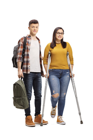 Full length portrait of a male student helping a female student walking with crutches isolated on white background Stock Photo