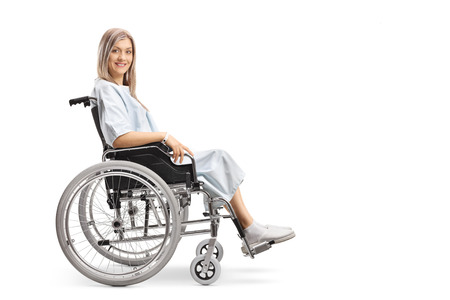 Young woman sitting min a wheelchair and looking at camera isolated on white background