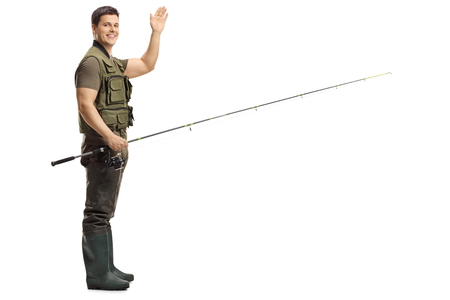 Full length shot of a young male fisherman holding a fishing rod and waving at the camera isolated on white background