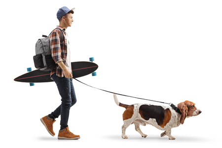 Full length profile shot of a young guy with a backpack and longboard walking a basset hound dog isolated on white background Stock Photo