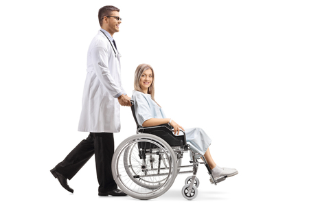 Full length shot of a young male doctor pushing a female patient in a wheelchair isolated on white background