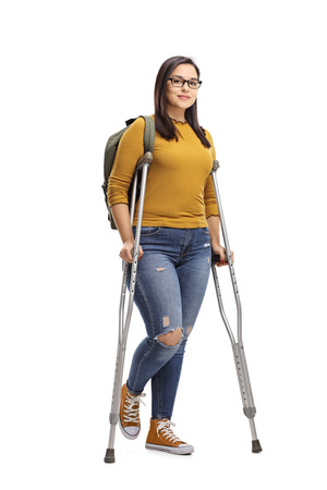 Full length portrait of a female student with crutches isolated on white background