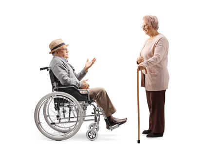 Full length profile shot of an elderly man sitting in a wheelchair and talking to a senior woman standing with a cane isolated on white background Imagens