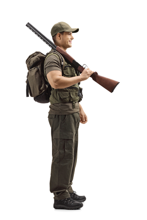 Full length profile shot of a young male hunter standing with a shotgun on his shoulder isolated on white background