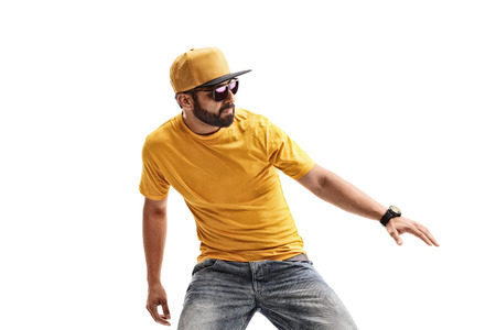 Male hipster in yellow t-shirt performing dancing moves  isolated on white background 免版税图像
