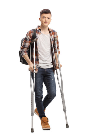 Full length portrait of a male student walking with crutches isolated on white background