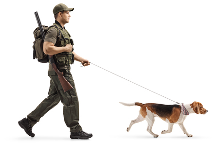 Full length profile shot of a hunter walking with a beagle dog on a leash isolated on white background
