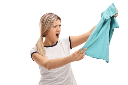 Angry woman holding a piece of clothing and looking at it isolated on white background