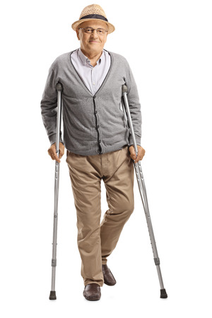 Full length portrait of a senior man walking with crutches and smiling at the camera isolated on white background