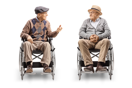 Two senior men in wheelchairs having a conversation isolated on white background