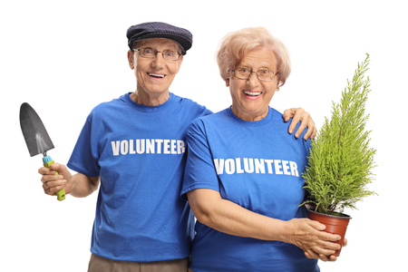 Senior man and woman volunteers holding a plant and a spade for planting isolated on white background