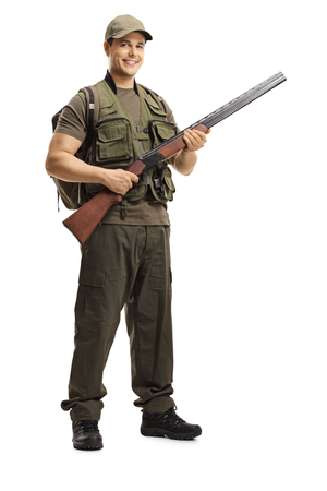 Full length portrait of a hunter posing with a shotgun isolated on white background