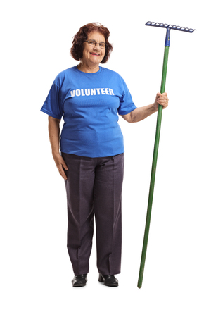 Full length portrait of a elderly woman volunteer with a rake isolated on white background