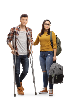 Full length portrait of a male student with crutches and a female student holding a backpack isolated on white background