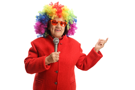 Elderly woman with a clown wig and a microphone isolated on white background