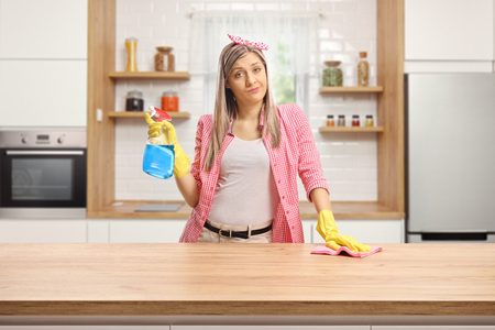 Jeune femme dans une cuisine fatiguée de nettoyer