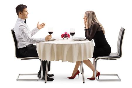 Disparo de perfil de longitud completa de un hombre joven hablando con una mujer joven en una mesa de restaurante aislada sobre fondo blanco Foto de archivo