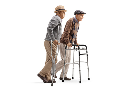 Full length profile shot of two elderly men walking with crutches and walker isolated on white background