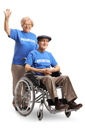 Senior volunteer woman waving and pushing a senior volunteer man in a wheelchair isolated on white background