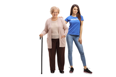 Volledig lengteportret van een bejaarde vrouw met een stok en een jonge vrouwelijke vrijwilliger die op witte achtergrond wordt geïsoleerd