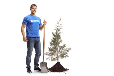 Retrato de cuerpo entero de un joven voluntario con una pala de pie junto a un árbol y suelo aislado sobre fondo blanco.