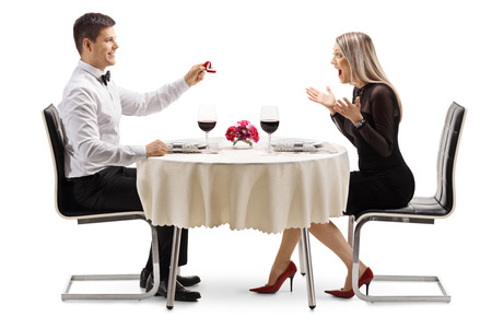 Full length profile shot of a young man proposing a marriage with a ring to a young woman at a restaurant table isolated on white background