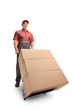 Male worker with a stack of boxes on a hand truck smiling at the camera isolated on white background