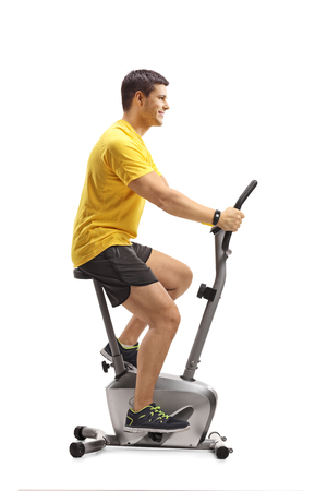 Full length shot of a young man cycling on a stationary bike isolated on white background
